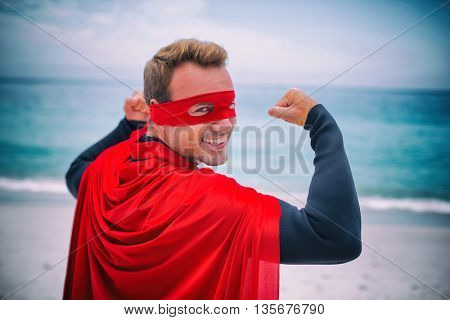Portrait of happy man in superhero costume flexing muscles at sea shore