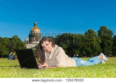 happy young student woman with laptop in city park