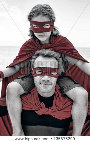 Portrait of confident father in superhero costume carrying son on shoulder at beach