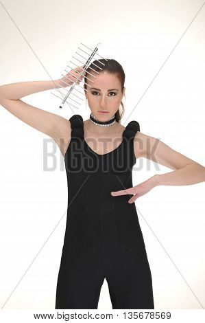 Girl keep to kitchen tools on head with black dress in studio