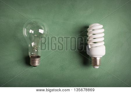 Electric bulbs on the green chalkboard (old and modern lamp)