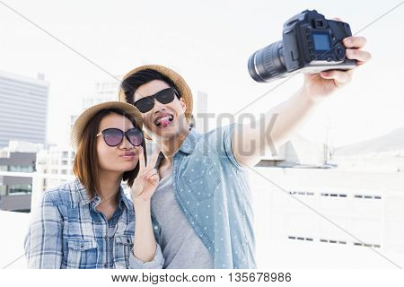 Happy young couple clicking a picture on camera outdoors