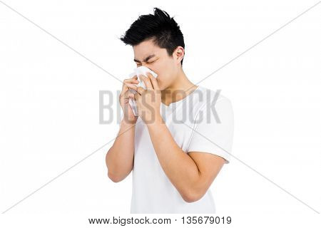 Young man wiping his nose with a tissue on white background
