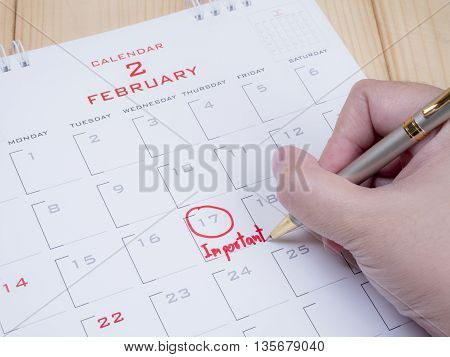 Woman hold a pen on right hand and write word important on calendar desk in February month with red ink