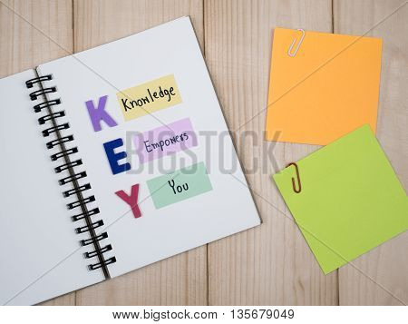 Word spell KEY and handwriting word Knowledge Empower You on notebook with wood background