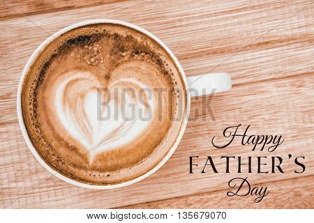 Happy fathers day message next to coffee on desk