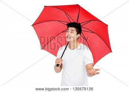 Young man with red umbrella on white background