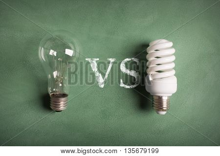 Electric bulbs on the green chalkboard (old and modern lamp). Image is describing the problem of decision about using old or modern tipe of amp