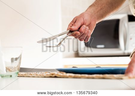 Close Up Of Hand Holding Fork And Knife At Table