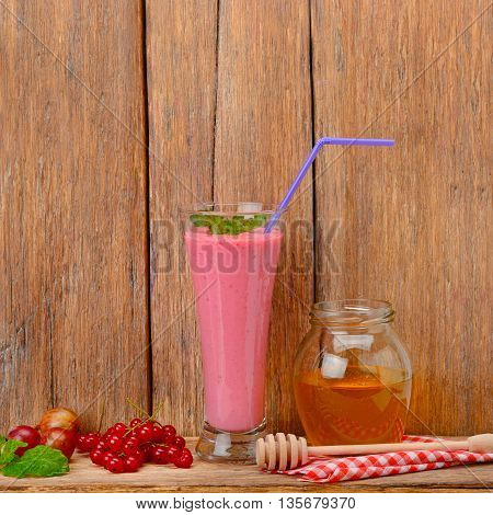 berry smoothie currants gooseberries and honey on a wooden surface