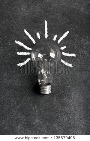 Transparent electric bulb on the black chalkboard (with rays)