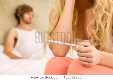 Worried woman waiting the pregnancy test result with boyfriend on background