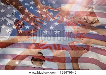 Volunteers with hands together against blue sky against close-up of american flag