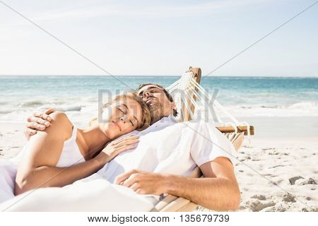 Couple sleeping in hammock on the beach