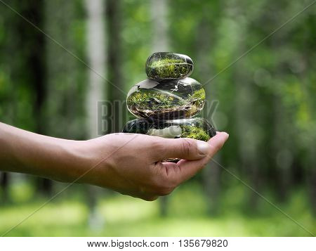 Cairn on a female hand. Background Natural green. Concept - calm stability ecology environment