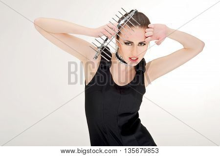 young women keep to kitchen tool on her head in studio