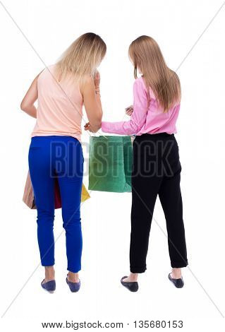 back view of  two women  with shopping bags. backside view of person.  Rear view people collection. Isolated over white background. Two girls blonde look in the paper bag.