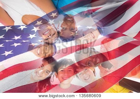 Waving flag of America against happy children forming huddle