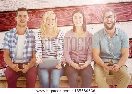 Portrait of smiling business people holding electronic gadgets against composite image of usa national flag