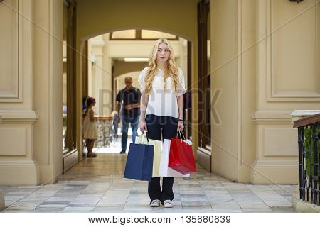 Young beautiful blonde woman with some shopping bags in the mall