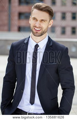 Portrait of a cheerful businessman in black suit, summer street outdoors