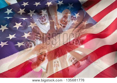 Cropped American flag against people stacking hands at health club