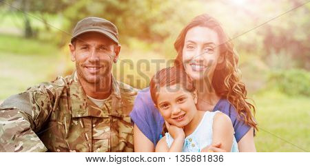 Portrait of smiling army man with family while sitting in park