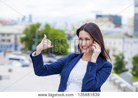 Beautiful brunette woman making a call me gesture, summer outdoors