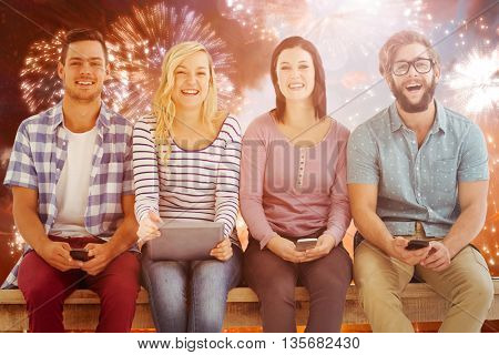 Portrait of smiling business people holding electronic gadgets against colourful fireworks exploding on black background