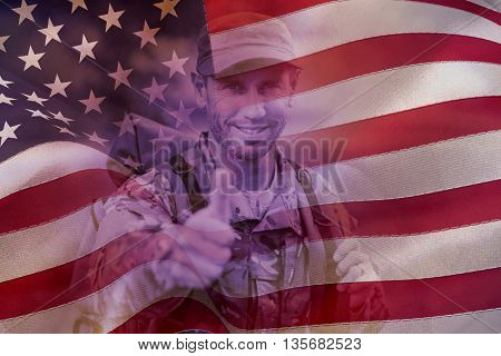 Portrait of happy army man with thumbs up against digitally generated united states national flag