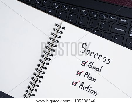 Handwriting word Success Goal Plan Action on blank notebook with laptop keyboard