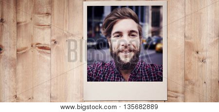 Happy hipster against wooden fence against wooden planks