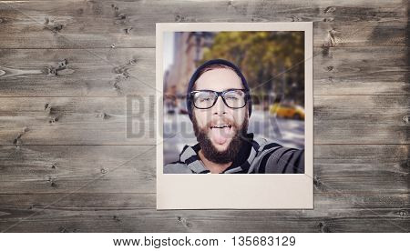 Happy hipster against wooden fence against bleached wooden planks background