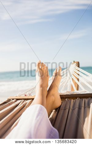 Woman lying in hammock on the beach