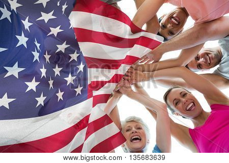 Focus on usa FLAG against happy sporty people holding hands together