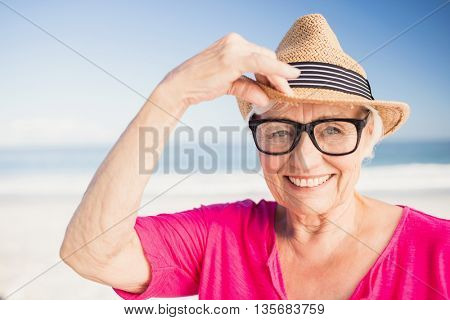 Smiling senior woman wearing straw hat on the beach