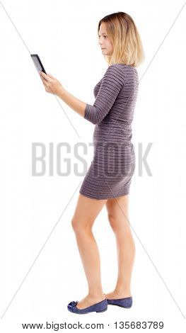 back view of standing young beautiful  girl with tablet computer in the hands of. girl  watching.  Isolated over white background. Girl in short dress stands sideways and read e-books.
