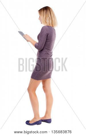 back view of standing young beautiful  girl with tablet computer in the hands of. girl  watching. Rear view people collection.  Girl in short dress stands sideways and writes in a Tablet PC.