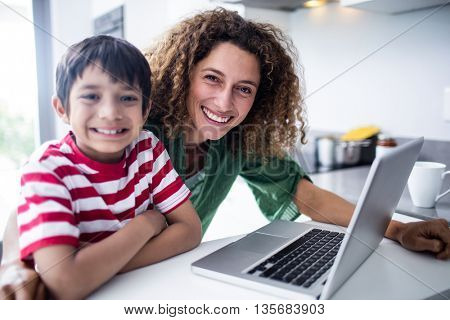 Portrait of mother and son using laptop in kitchen at home