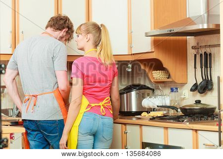 Couple woman and man in apron cooking preparing dinner food in kitchen together.