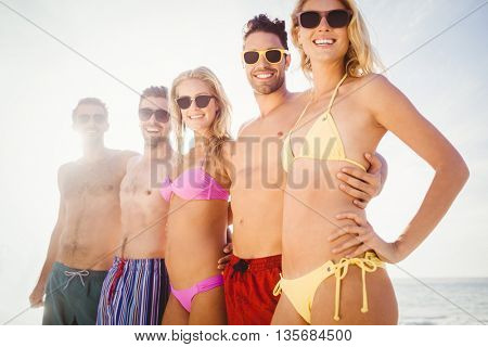 Smiling friends standing in line on the beach