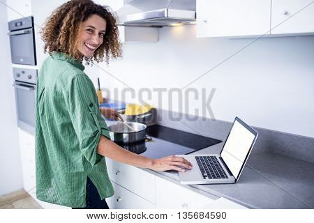Portrait of woman working on laptop while cooking in kitchen