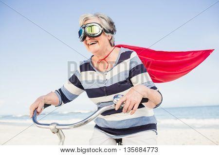 Senior superwoman on a bike on the beach