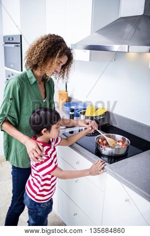 Mother and son cooking in kitchen at home
