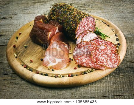 Sliced smoked sausage with spices on a wooden background