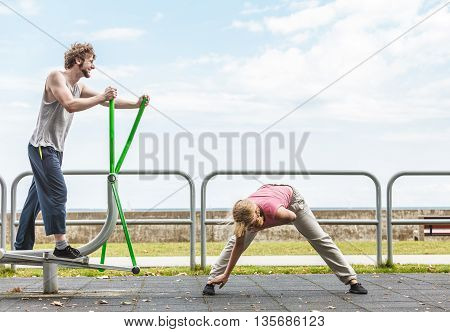 Man Exercising On Elliptical Trainer And Woman.