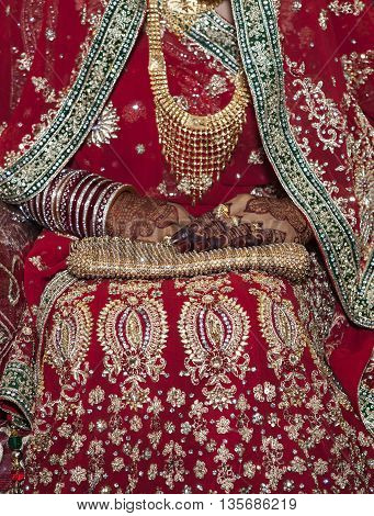 Close-up shot of a mid section of a female wearing elegant bangles and rings in hand.