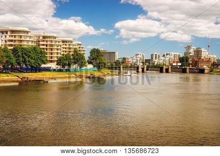 Modern residential area on the riverbank. Idyllic warm toned landscape at sunny day. Saint Petersburg Russia