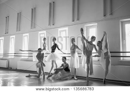 Thr seven ballerinas at ballet rack in the rehearsal hall of the theater. The black and white image