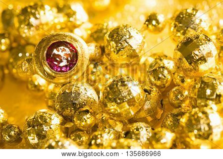 Luxury golden jewelry pearls and ring with gem on yellow background.